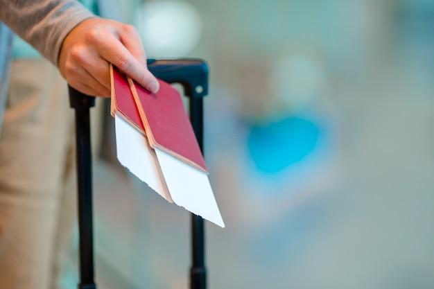 Primo piano dei passaporti e del passaggio di imbarco della tenuta dell'uomo all'aeroporto