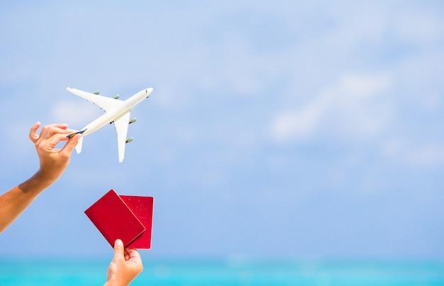 Primo piano dei passaporti e dell'aeroplano bianco il mare