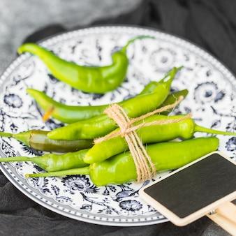 Primo piano dei peperoncini verdi freschi legati e dell'ardesia in bianco sul piatto