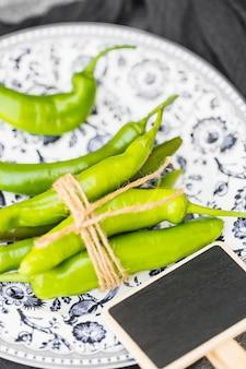 Primo piano dei peperoncini verdi legati e dell'ardesia in bianco sul piatto