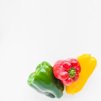 Primo piano dei peperoni dolci freschi variopinti su fondo bianco