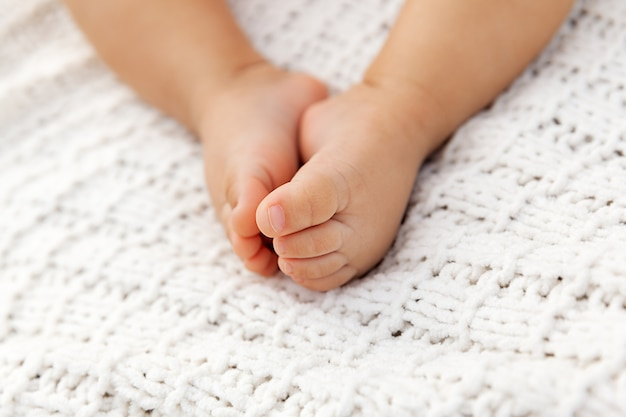 Primo piano dei piedi adorabili del bambino sulla coperta tricottata come fondo in un fuoco selettivo, gambe infantili a luce naturale