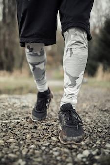 Primo piano dei piedi dell'atleta maschio che corrono sulla traccia della ghiaia