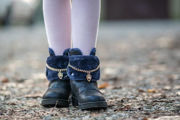 Primo piano dei piedi della ragazza del bambino in ghette rosa e scarpe alla moda di autunno che stanno all'aperto in tempo soleggiato dell'autunno.