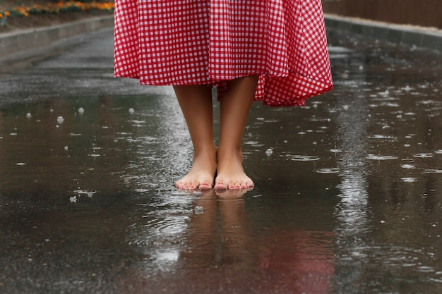 Primo piano dei piedi di una ragazza che ballano in una pozzanghera dopo una pioggia estiva.