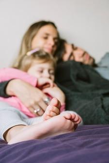 Primo piano dei piedi di una ragazza che si rilassano con i loro genitori