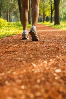 Primo piano dei piedi e delle scarpe del corridore di un atleta che corrono avanti