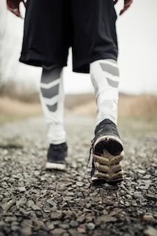 Primo piano dei piedi maschili dell'atleta in scarpe da corsa che pareggiano sulla strada