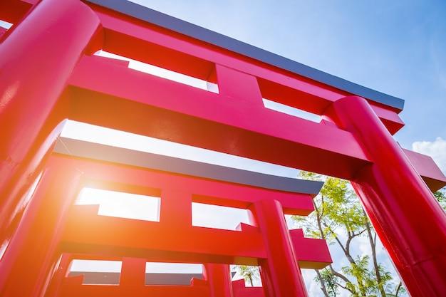 Primo piano dei portoni rossi di torii con la priorità bassa del cielo blu.