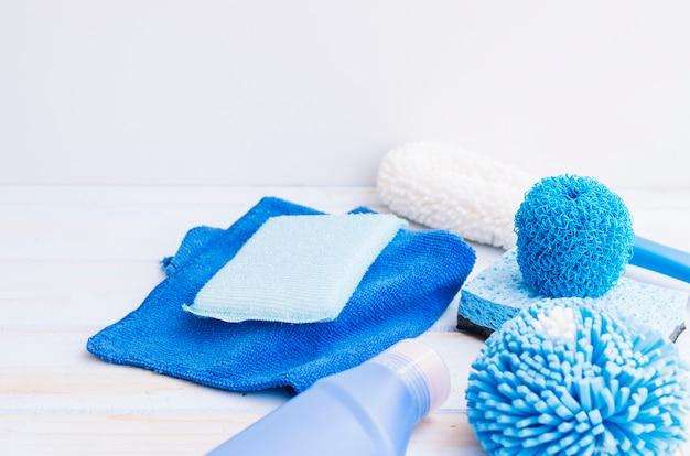 Primo piano dei rifornimenti di pulizia blu sullo scrittorio