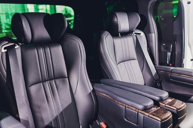 Primo piano dei sedili posteriori in pelle nera con poggiapiedi. interni auto moderne.