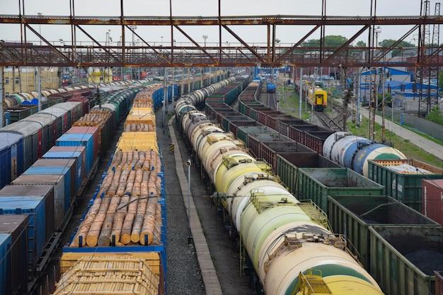Primo piano dei treni merci. vista aerea dei treni sulla stazione ferroviaria. carri con legno e olio. autunno