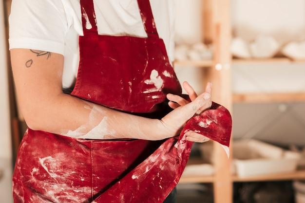 Primo piano dei vasai femminili che puliscono le sue mani con il grembiule rosso
