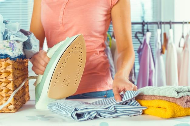 Primo piano dei vestiti rivestenti di ferro della donna sull'asse da stiro