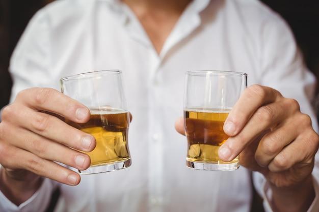 Primo piano dei vetri di colpo del whiskey della tenuta del barista al contatore della barra