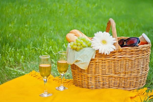 Primo piano dei vetri di vino sulla copertura gialla, sul canestro di picnic con alimento e sul fiore sull'erba verde