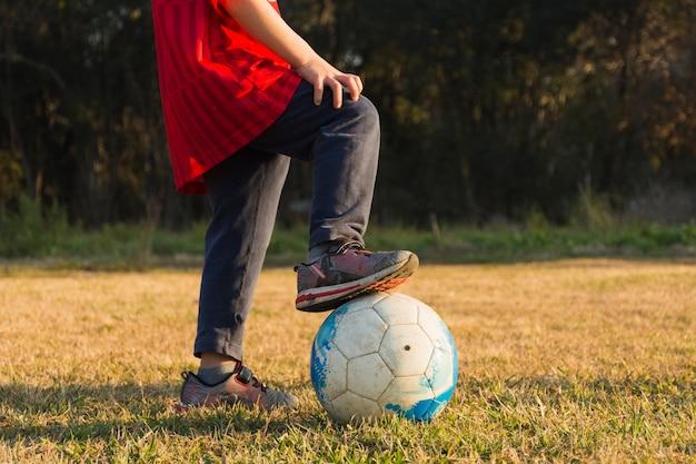 Primo piano del bambino che gioca con il calcio nel parco