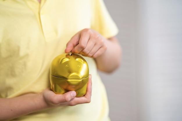 Primo piano del bambino che mette le monete nel porcellino salvadanaio.