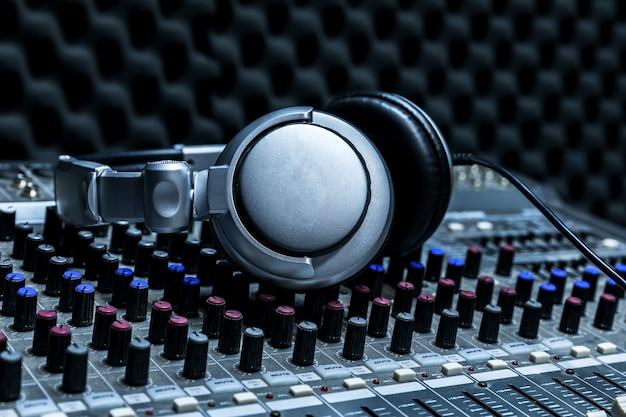 Primo piano del banco di controllo dello studio di registrazione boutique, cuffie dj per disco professionale, attrezzatura per studio di registrazione audio, mixer e cuffie dj