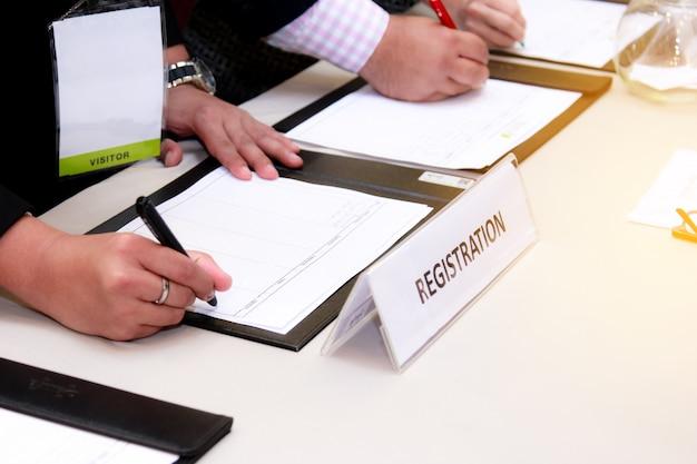 Primo piano del banco di registrazione di fronte al centro congressi con uomo d'affari