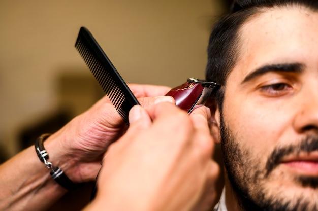 Primo piano del barbiere che dà a cliente un taglio di capelli