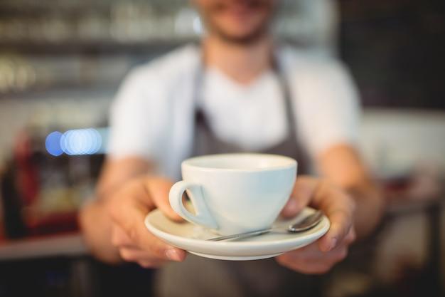 Primo piano del barista che serve caffè alla caffetteria