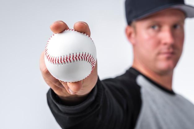 Primo piano del baseball tenuto in mano