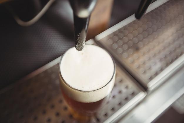 Primo piano del bicchiere di birra con schiuma