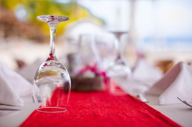 Primo piano del bicchiere di vino sulla tavola apparecchiata per il banchetto al tramonto