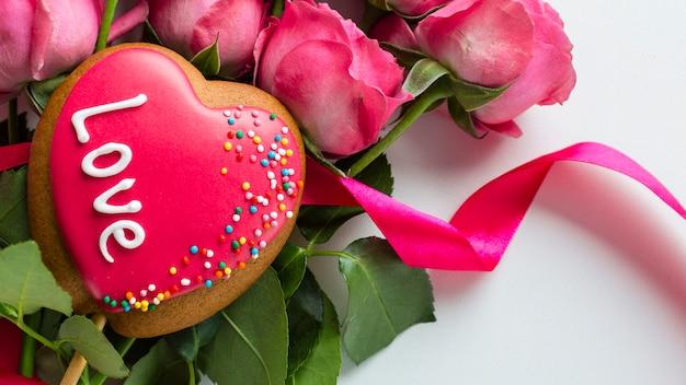 Primo piano del biscotto a forma di cuore sulle rose