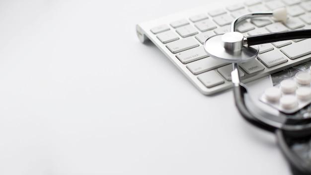 Primo piano del blister e dello stetoscopio della pillola sulla tastiera sopra superficie bianca