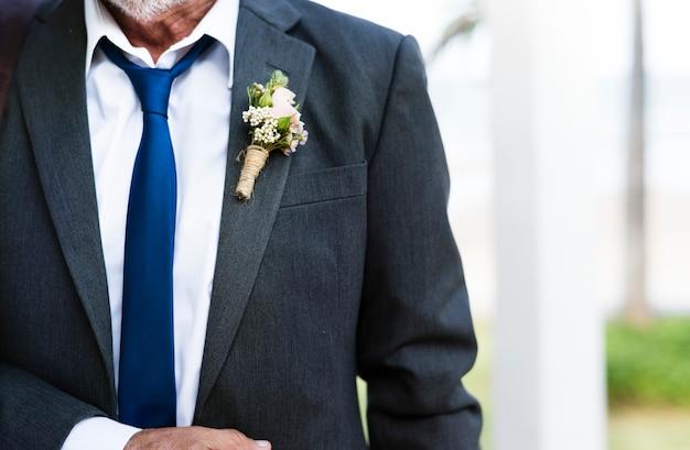 Primo piano del boutonnière dello sposo sul risvolto del vestito