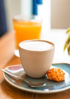 Primo piano del caffè del cappuccino con il biscotto ed il cucchiaio