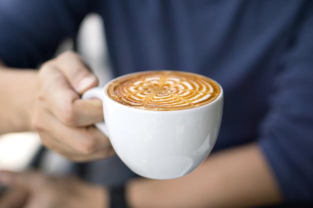 Primo piano del caffè maschio della tenuta della mano