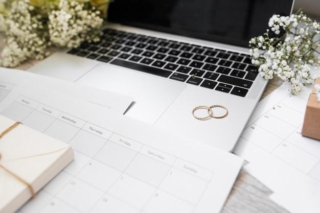 Primo piano del calendario; fedi nuziali; fiori e computer portatile sulla scrivania