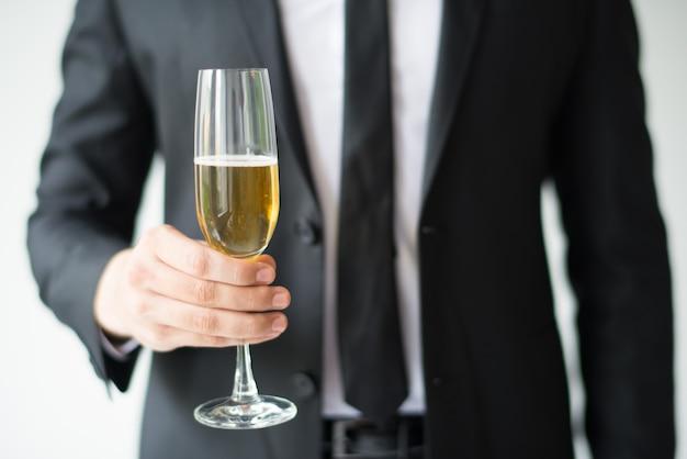 Primo piano del calice della holding dell'uomo di affari con champagne