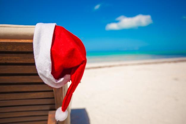 Primo piano del cappello di santa sulla sedia longue alla spiaggia caraibica tropicale