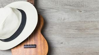 Primo piano del cappello sopra la chitarra contro fondo di legno