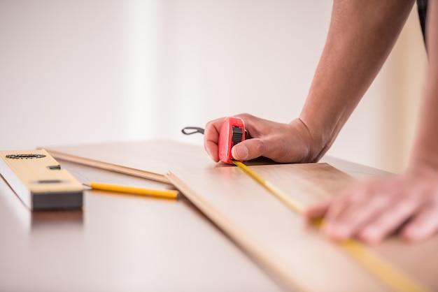 Primo piano del carpentiere che misura plancia di legno.