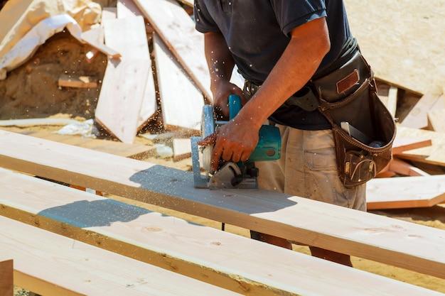 Primo piano del carpentiere che usando una sega circolare per tagliare un grande bordo di legno