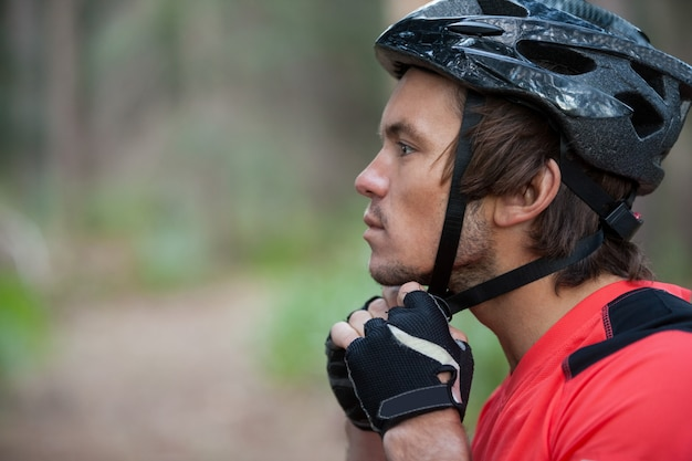 Primo piano del casco d'uso della bicicletta del ciclista in mountain-bike maschio