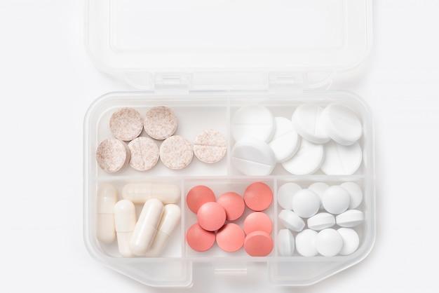 Primo piano del caso pillola con varie pillole, capsule