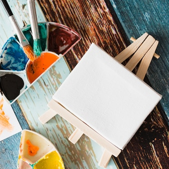 Primo piano del cavalletto bianco bianco minimo con la tavolozza della pittura e pennello su superficie di legno