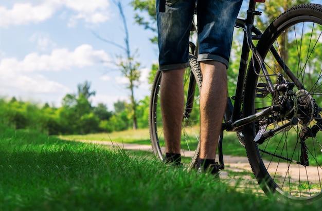 Primo piano del ciclista e della bici sullo spazio abbandonato della copia della strada del villaggio