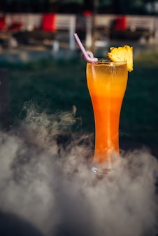Primo piano del cocktail alcolico sul bancone del bar in una nuvola di fumo.