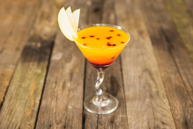 Primo piano del cocktail nel bicchiere da martini sulla scrivania in legno