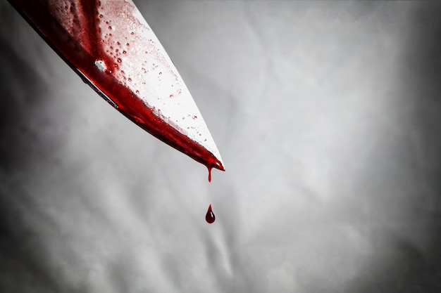 Primo piano del coltello imbrattato di sangue e ancora gocciolante.