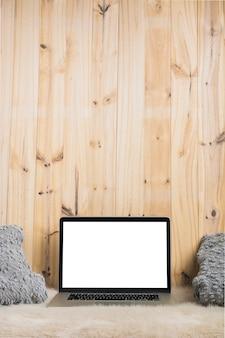 Primo piano del computer portatile e cuscino su morbida pelliccia contro il contesto in legno
