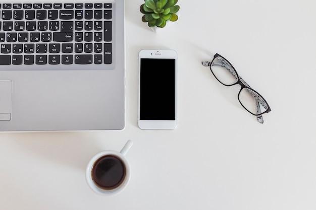 Primo piano del computer portatile e del telefono cellulare con la tazza di caffè e gli occhiali