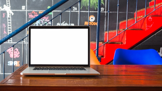 Primo piano del computer portatile sullo scrittorio di legno davanti alla scala